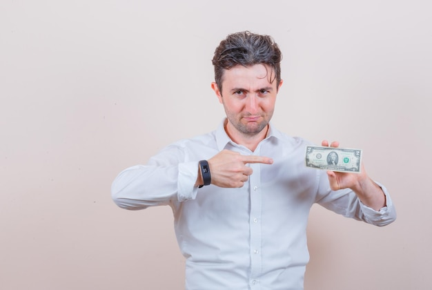 달러 지폐를 가리키고 긍정적 인 찾고 흰 셔츠에 젊은 남자