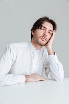 회색 벽에 격리된 책상에 앉아 있는 동안 자고 있는 흰 셔츠를 입은 청년