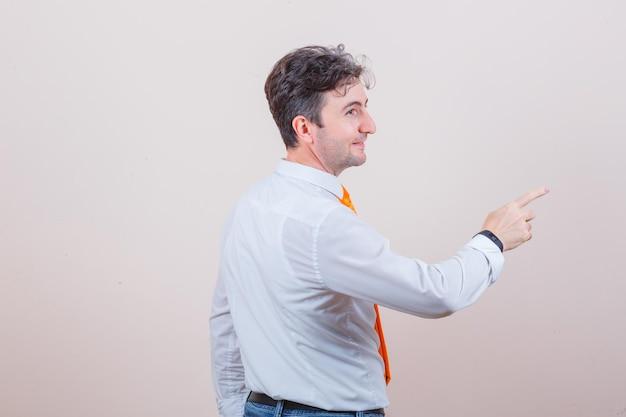 흰 셔츠, 넥타이, 청바지 멀리 가리키는 쾌활한 찾고 젊은 남자.