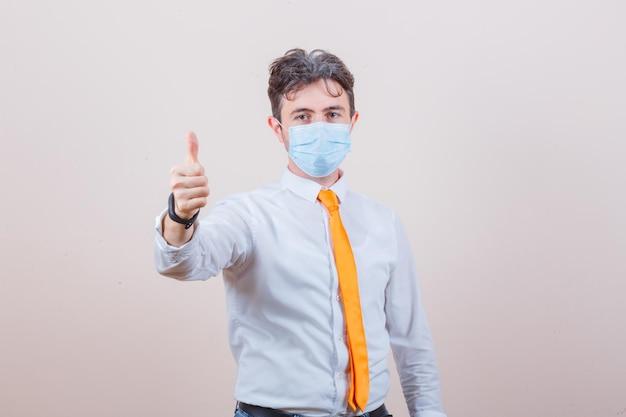Молодой человек в белой рубашке, галстуке, маске показывает палец вверх и выглядит довольным Бесплатные Фотографии