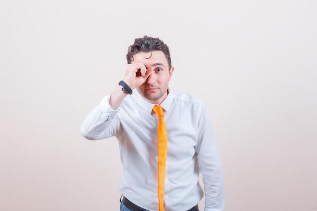 白いシャツを着た若い男、目にokのサインを示し、好奇心旺盛に見えるネクタイ