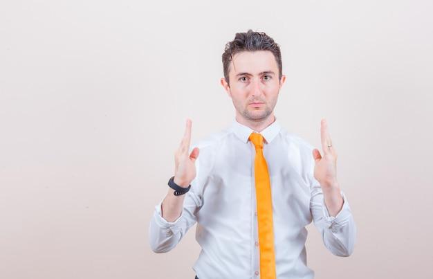 흰 셔츠에 젊은 남자, 넥타이 크기 기호를 표시하고 자신감을 찾고