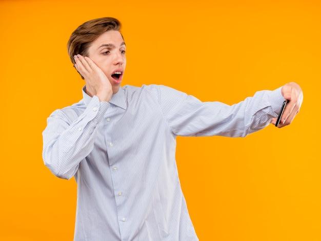 オレンジ色の背景の上に立って驚いて見えるビデオ通話を持っているスマートフォンを使用して白いシャツを着た若い男