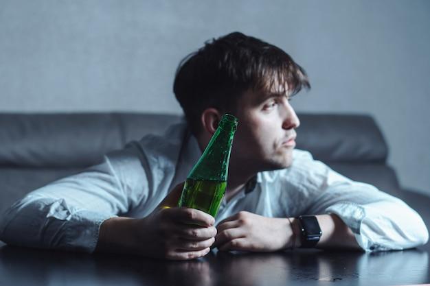 Молодой человек в белой рубашке с зеленой пивной бутылкой пьет дома