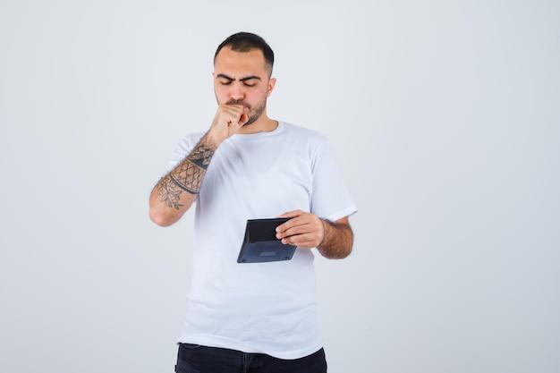 電卓を保持し、口に拳を保持し、真剣に見える白いtシャツと黒のズボンの若い男