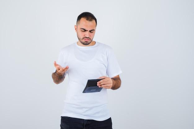 흰색 티셔츠와 검은 색 바지에 젊은 남자가 계산기를 들고 손을 뻗어 방식으로 질문하고 당황하게 보입니다.