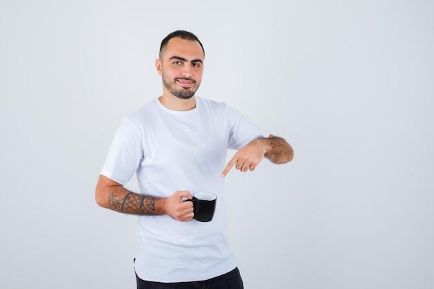 お茶のカップを保持し、それを指して幸せそうに見える白いtシャツと黒のズボンの若い男