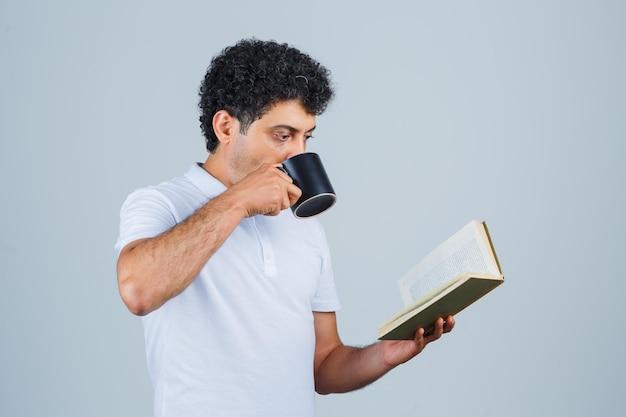 Молодой человек в белой футболке и джинсах пьет чашку чая во время чтения книги и выглядит счастливым, вид спереди.