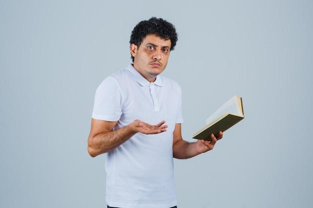 흰색 티셔츠와 청바지를 입은 청년이 책을 들고 손을 뻗어 질문하는 방식으로 손을 뻗고 당황한 표정을 짓고 있습니다.
