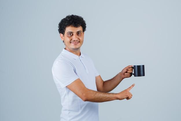 흰색 티셔츠와 청바지를 입은 청년은 차 한 잔을 들고 그것을 가리키고 행복해 보이는 앞모습을 보고 있습니다.