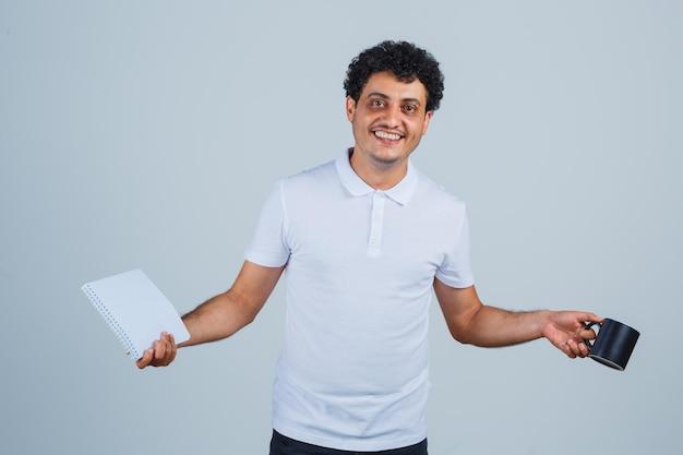 흰색 티셔츠와 청바지를 입은 젊은 남자가 차 한 잔을 들고 노트북을 보여주고 행복해 보이는 앞모습을 보고 있습니다.