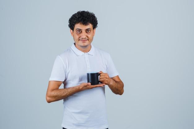 흰색 티셔츠와 청바지를 입은 청년이 양손으로 차 한 잔을 들고 행복해 보이는 앞모습.