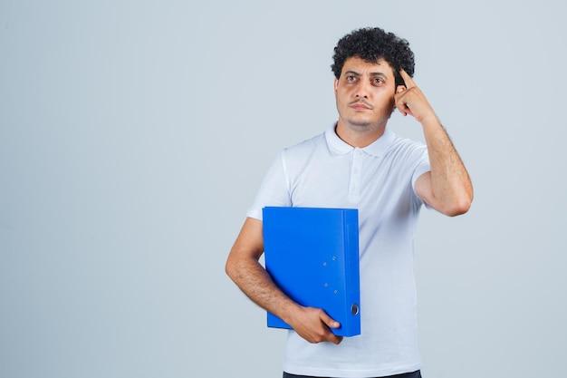 흰색 티셔츠와 청바지를 입은 젊은 남자가 파일 폴더를 들고 관자놀이에 손가락을 대고 수심에 찬 앞모습을 보고 있습니다.