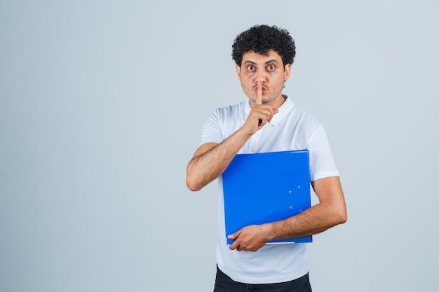 Молодой человек в белой футболке и джинсах держит папку с файлами и показывает жест молчания и выглядит серьезным, вид спереди.
