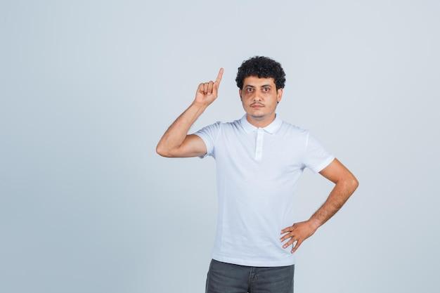 Молодой человек в белой футболке и джинсах держит руку на талии, поднимая указательный палец в жесте эврики и выглядит разумно, вид спереди.