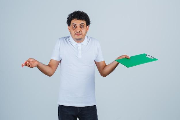 Молодой человек в белой футболке и джинсах держит блокнот и ручку, пожимает плечами и выглядит сбитым с толку, вид спереди.