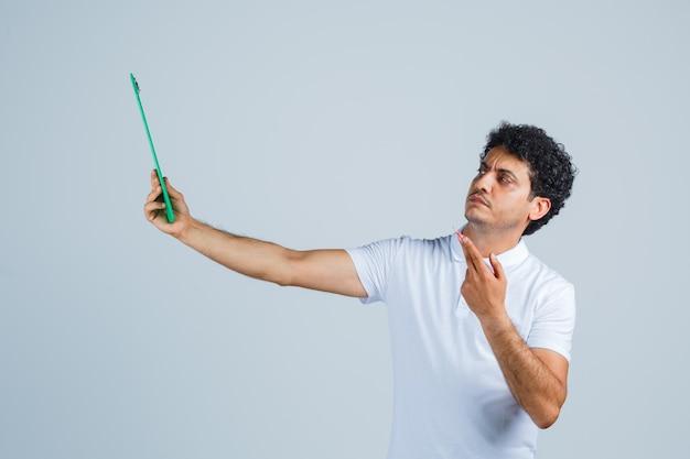 Молодой человек в белой футболке и джинсах держит блокнот и ручку, думает о чем-то и смотрит задумчиво, вид спереди.