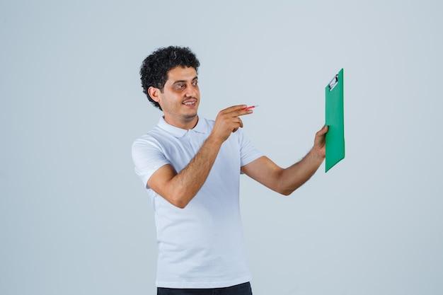 白いtシャツとジーンズの若い男がノートを保持し、ペンでそれを指して、幸せそうに見える、正面図。