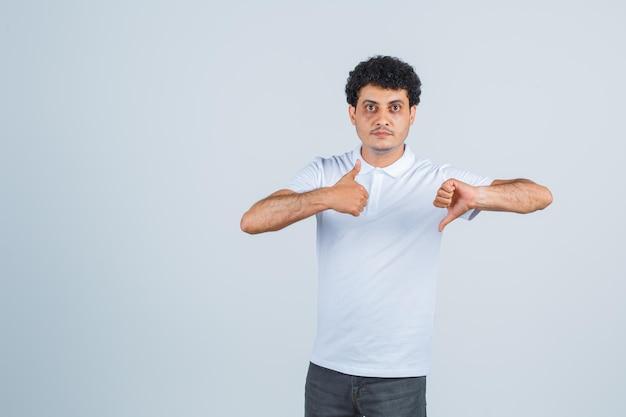 Молодой человек в белой футболке и джинсах показывает большие пальцы рук вверх и вниз обеими руками и выглядит серьезным, вид спереди.
