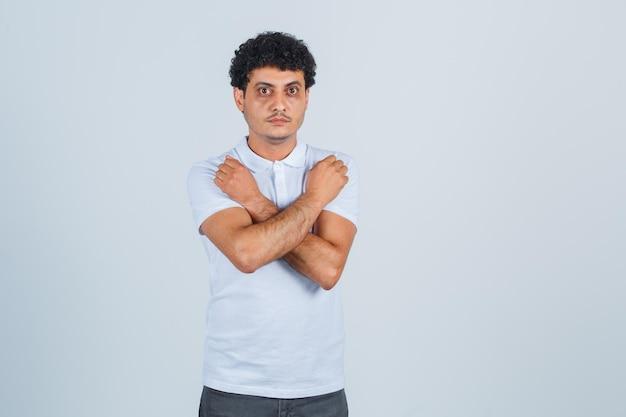 Молодой человек в белой футболке и джинсах показывает x или жест ограничения и выглядит серьезным, вид спереди.