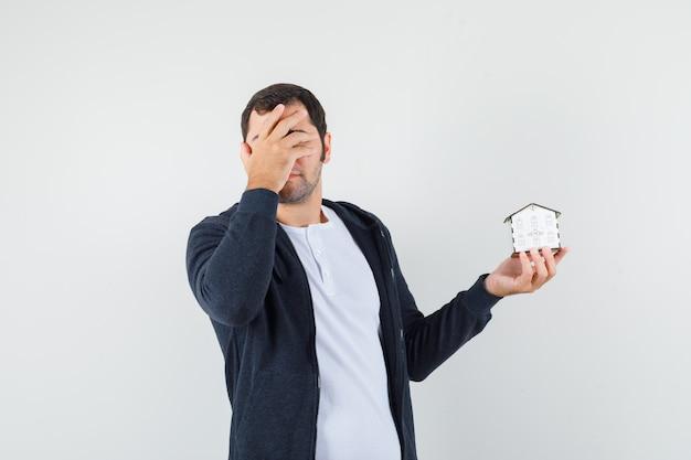 白いtシャツとジップフロントの黒いパーカーの若い男が家のモデルを保持し、手で顔を覆い、急いでいるように見える、正面図。