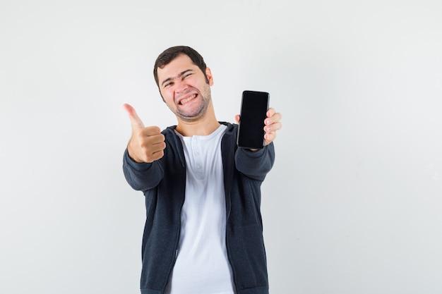 白いtシャツとジッパー付きの若い男-スマートフォンを保持しているフロントの黒いパーカー、親指を上に表示し、幸せそうに見える、正面図。