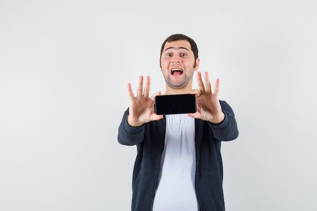 両手でスマートフォンを保持し、幸せそうに見える、正面図の白いtシャツとジップフロントの黒いパーカーの若い男。