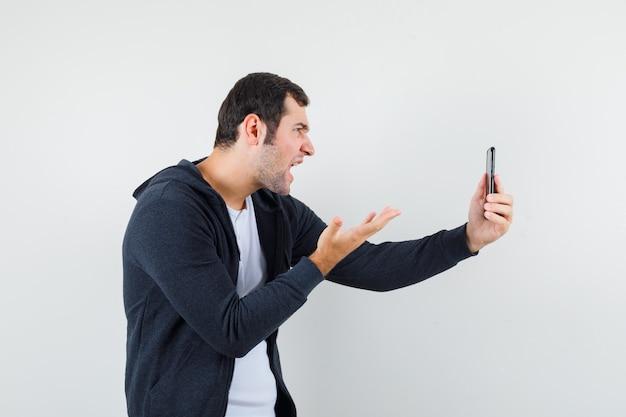 흰색 티셔츠와 zip-front 검은 까마귀에 젊은 남자가 videocall을 통해 누군가에게 이야기하고 화난, 정면보기를보고 있습니다.