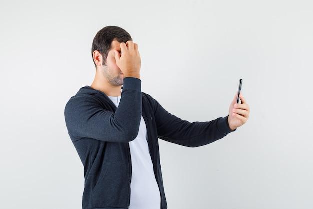 白いtシャツとジップフロントの黒いパーカーを着た若い男がビデオコールで誰かと話し、幸せそうに見える正面図。