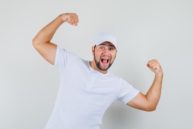 흰색 티셔츠에 젊은 남자, 그의 팔 근육을 보여주는 모자와 강력한, 전면보기를 찾고.
