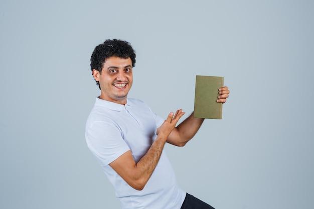 흰색 티셔츠를 입은 젊은 남자가 책을 들고 쾌활하고 앞모습을 보고 있습니다.