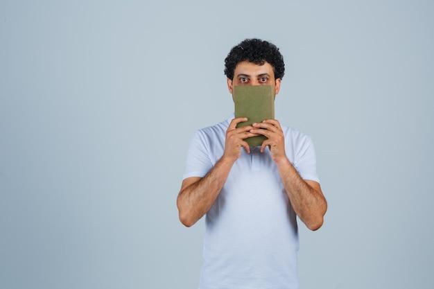 흰색 티셔츠를 입은 젊은 남자가 책을 들고 생각에 잠긴 모습을 보고 있습니다.