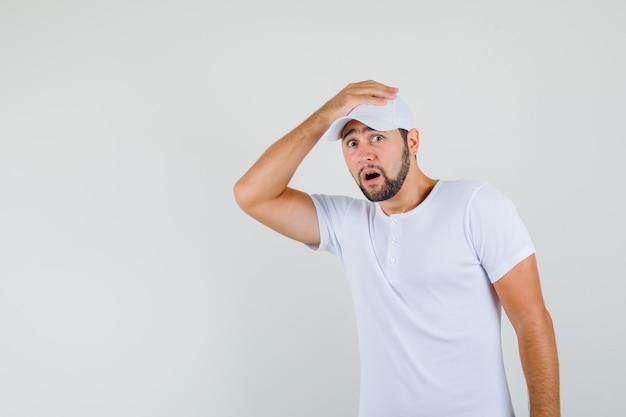 彼の頭に手をつないで、怖がって、正面図を見て白いtシャツの若い男。
