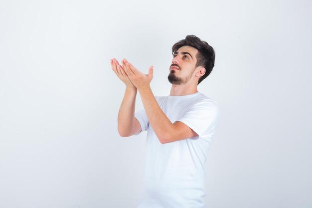 祈りのジェスチャーで手をつないで、希望に満ちた白いtシャツの若い男