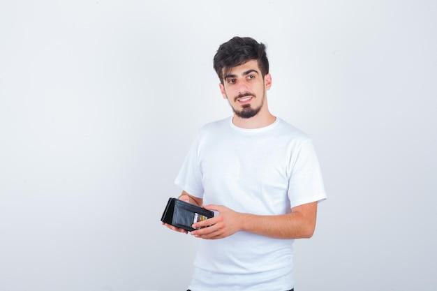 財布を持って物思いにふける白いtシャツの若い男