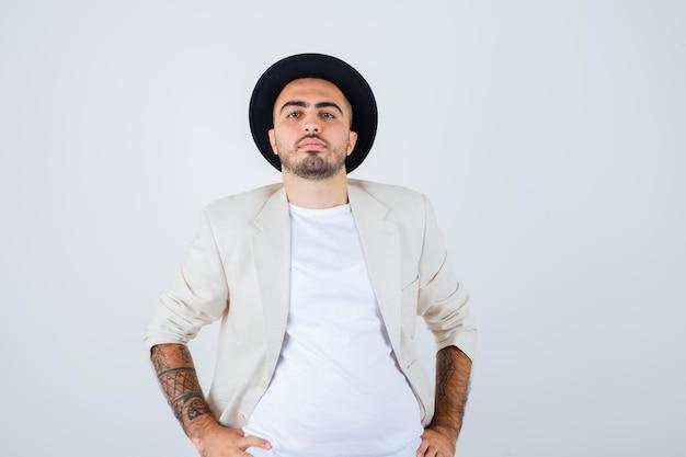 Молодой человек в белой футболке, куртке и черной шляпе, взявшись за руки на талии и глядя серьезно, вид спереди.