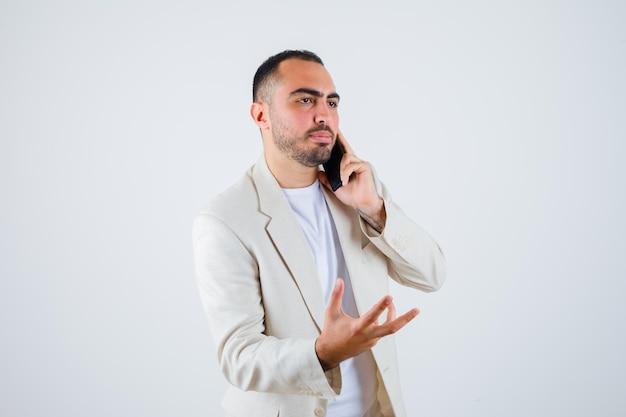 白いtシャツを着た若い男、電話に話しかけ、何かを持って真剣に見えるように手を伸ばして、正面図。