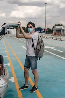 Молодой человек в белой футболке, джинсовых шортах, солнцезащитных очках и хирургической маске с рюкзаком на спине. через вид автомобиля