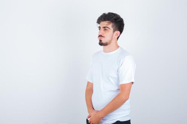 目をそらし、物思いにふける白いtシャツの若い男