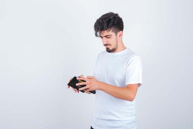 Молодой человек в белой футболке смотрит в бумажник и смотрит задумчиво