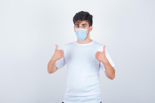 白いtシャツを着た若い男、二重の親指を上に示し、自信を持って見えるマスク