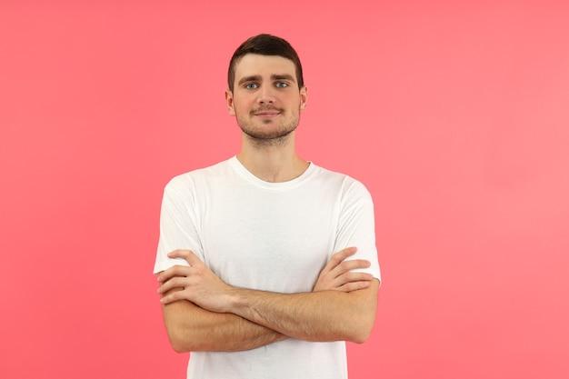 분홍색 배경에 흰색 티셔츠를 입은 젊은 남자.