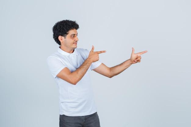白いtシャツを着た若い男、銃のジェスチャーを示し、自信を持って見えるズボン、正面図。