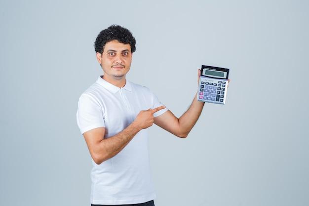 Молодой человек в белой футболке, указывая на калькулятор и уверенно глядя, вид спереди.