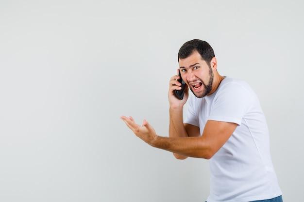 電話で話している間、怒っている、正面図を見て叫んでいる白いtシャツの若い男。テキスト用のスペース