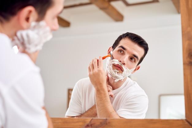 Молодой человек в белой футболке бреется, стоя возле зеркала в ванне утром