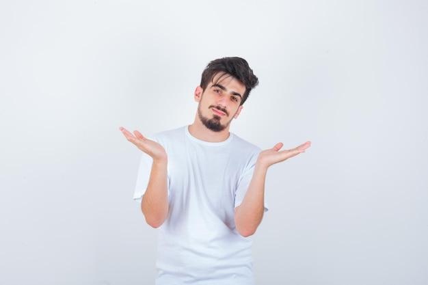無力なジェスチャーを示し、混乱しているように見える白いtシャツの若い男
