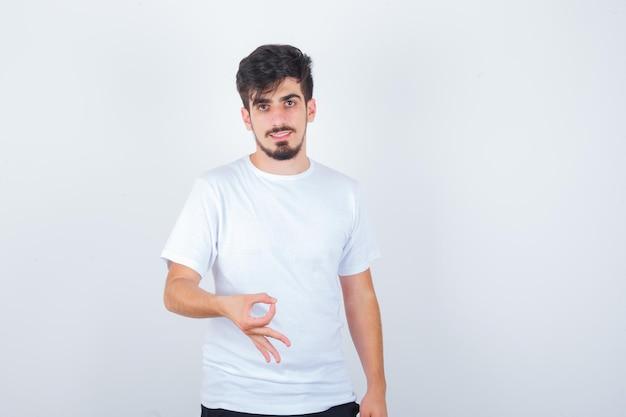 大丈夫なジェスチャーを示し、自信を持って見える白いtシャツの若い男