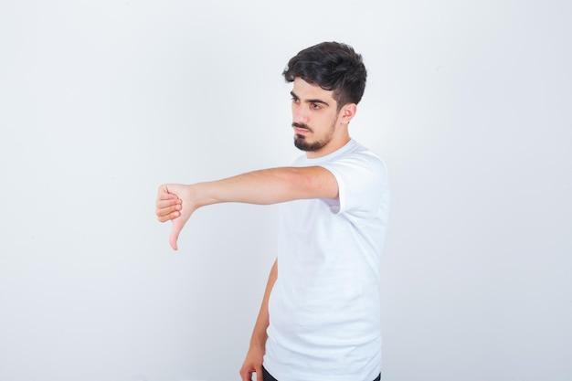 親指を下に向けて自信を持って見える白いtシャツの若い男