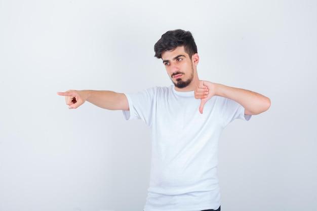 親指を下に向け、向きを変え、自信を持って見える白いtシャツの若い男